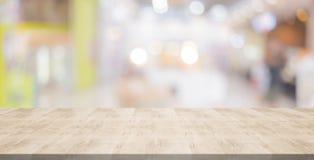 Ξύλινη επιτραπέζια κορυφή στο θολωμένο υπόβαθρο από τη λεωφόρο αγορών, διαστημικό φ Στοκ Φωτογραφία