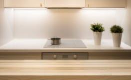 Ξύλινη επιτραπέζια κορυφή στο νησί κουζινών στο σύγχρονο απλό εγχώριο εσωτερικό στοκ εικόνες