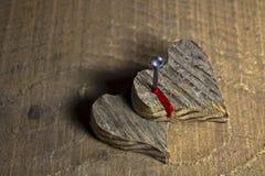 Ξύλινη καρδιά δύο που καρφώνεται και που αιμορραγεί Στοκ Φωτογραφία