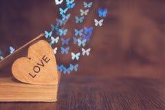 Ξύλινη καρδιά με ένα παλαιό βιβλίο στον πίνακα και ένα υπόβαθρο του bokeh φιαγμένο από πεταλούδες βαλεντίνος ημέρας s στοκ εικόνα