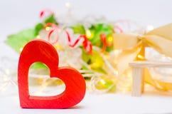 Ξύλινη καρδιά με ένα τόξο σε έναν πάγκο σε ένα άσπρο υπόβαθρο βαλεντίνος ημέρας s Η έννοια της αγάπης ρωμανικός κομψότητα Στοκ Φωτογραφίες