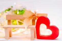 Ξύλινη καρδιά με ένα τόξο σε έναν πάγκο σε ένα άσπρο υπόβαθρο Ημέρα βαλεντίνων ` s η έννοια της αγάπης ρωμανικός Στοκ Εικόνες