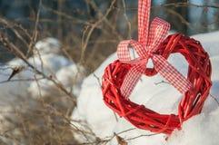 Ξύλινη καρδιά με την κορδέλλα στο χιόνι, υπόβαθρο στην ημέρα των εραστών Στοκ Εικόνες