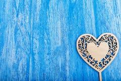 Ξύλινη καρδιά που χαράζεται σε ένα μπλε ξύλινο υπόβαθρο Στοκ Φωτογραφία