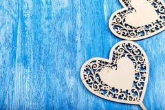 Ξύλινη καρδιά που χαράζεται σε ένα μπλε ξύλινο υπόβαθρο Στοκ φωτογραφία με δικαίωμα ελεύθερης χρήσης