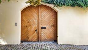 Ξύλινη καφετιά πόρτα πυλών αψίδων, άσπροι τοίχοι, ταλαντεύοντας κισσός Στοκ φωτογραφίες με δικαίωμα ελεύθερης χρήσης