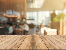 Ξύλινη κενή επιτραπέζια κορυφή πινάκων επάνω του θολωμένου υποβάθρου Καφετής ξύλινος πίνακας προοπτικής πέρα από τη θαμπάδα στο υ στοκ φωτογραφίες με δικαίωμα ελεύθερης χρήσης