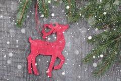 Ξύλινη κόκκινη διακόσμηση ελαφιών Χριστουγέννων στο ξύλινο υπόβαθρο Συρμένο χιόνι Στοκ φωτογραφία με δικαίωμα ελεύθερης χρήσης