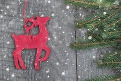 Ξύλινη κόκκινη διακόσμηση ελαφιών Χριστουγέννων στο ξύλινο υπόβαθρο Συρμένο χιόνι Στοκ εικόνα με δικαίωμα ελεύθερης χρήσης