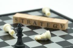 Ξύλινη λέξη που τοποθετείται στη σκακιέρα με ένα κομμάτι σκακιού στο πίσω ΝΕ Στοκ Φωτογραφίες