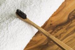 Ξύλινη οδοντόβουρτσα και άσπρη πετσέτα Στοκ φωτογραφίες με δικαίωμα ελεύθερης χρήσης
