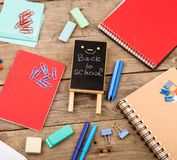 Ξύλινη πινακίδα με την επιγραφή & x22 Πίσω στο school& x22  κοντινά σημειωματάρια, έγγραφα και άλλα χαρτικά στον καφετή ξύλινο πί στοκ εικόνες με δικαίωμα ελεύθερης χρήσης