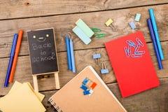 Ξύλινη πινακίδα με την επιγραφή & x22 Πίσω στο school& x22  κοντινά σημειωματάρια, έγγραφα και άλλα χαρτικά στον καφετή ξύλινο πί στοκ φωτογραφία
