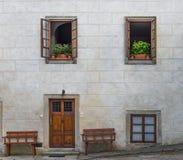 Ξύλινη πόρτα στον κενό συγκεκριμένο γκρίζο τοίχο φραγμών με τον ανώτερο δύο WI Στοκ Εικόνες