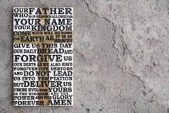 Ξύλινη χαρασμένη λέξη της προσευχής Λόρδου ` s στο γκρίζο συγκεκριμένο υπόβαθρο Στοκ εικόνες με δικαίωμα ελεύθερης χρήσης