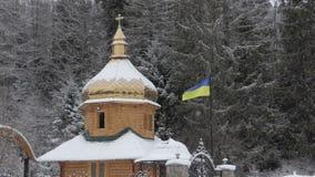 Ξύλινη χριστιανική Ορθόδοξη Εκκλησία με μια ουκρανική σημαία Carpathians απόθεμα βίντεο