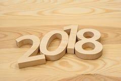 Ξύλινοι αριθμοί που διαμορφώνουν το 2018, χαρασμένος από το ελαφρύ ξύλο στο backg Στοκ Εικόνες
