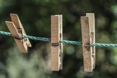 Ξύλινοι γόμφοι ενδυμάτων που κρεμιούνται στο σχοινί στον κήπο Στοκ Εικόνα
