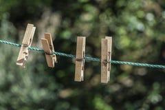 Ξύλινοι γόμφοι ενδυμάτων που κρεμιούνται στο σχοινί στον κήπο Στοκ εικόνα με δικαίωμα ελεύθερης χρήσης