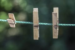 Ξύλινοι γόμφοι ενδυμάτων που κρεμιούνται στο σχοινί στον κήπο Στοκ Εικόνες