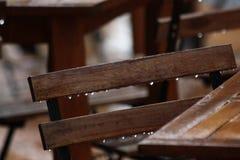Ξύλινοι καρέκλα και πίνακας από έναν καφέ στη βροχή Υγρά αστικά έπιπλα στοκ φωτογραφία