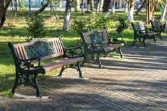 Ξύλινοι πάγκοι πάρκων σε ένα πάρκο μια όμορφη ηλιόλουστη ημέρα Στοκ Φωτογραφία