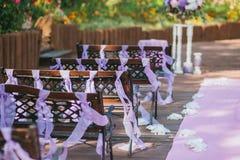 Ξύλινοι πάγκοι στην περιοχή γαμήλιας τελετής στον κήπο, που διακοσμείται με τις πορφυρές κορδέλλες στοκ φωτογραφίες