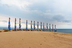 Ξύλινοι τελετουργικοί στυλοβάτες με τις ζωηρόχρωμες κορδέλλες Hadak στο ακρωτήριο Burkhan baikal λίμνη baikal λίμνη olkhon Ρωσία  Στοκ φωτογραφίες με δικαίωμα ελεύθερης χρήσης