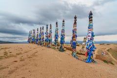 Ξύλινοι τελετουργικοί στυλοβάτες με τις ζωηρόχρωμες κορδέλλες Hadak στο ακρωτήριο Burkhan baikal λίμνη baikal λίμνη olkhon Ρωσία  Στοκ φωτογραφία με δικαίωμα ελεύθερης χρήσης