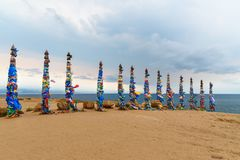 Ξύλινοι τελετουργικοί στυλοβάτες με τις ζωηρόχρωμες κορδέλλες Hadak στο ακρωτήριο Burkhan baikal λίμνη baikal λίμνη olkhon Ρωσία  Στοκ Φωτογραφίες
