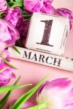 Ξύλινοι φραγμοί με την ημερομηνία όπως την 1η Μαρτίου με τις πορφυρές τουλίπες Στοκ Εικόνα