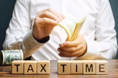 Ξύλινοι φραγμοί με το φορολογικό χρόνο λέξης και φορολογούμενος με χρήματα Ετήσιοι φόροι ιδιοκτησίας/εισοδήματος Η έννοια της πλη στοκ εικόνα