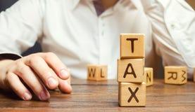 Ξύλινοι φραγμοί με το φόρο λέξης και μια συνεδρίαση επιχειρηματιών στον πίνακα Λήψη της σωστής απόφασης πληρώστε το φορολογικό χρ στοκ φωτογραφία με δικαίωμα ελεύθερης χρήσης