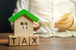 Ξύλινοι φραγμοί με το φόρο λέξης, σπίτι με τα χρήματα στα χέρια ενός επιχειρηματία Η έννοια της πληρωμής του φόρου για την κατοικ στοκ εικόνες