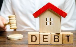 Ξύλινοι φραγμοί με το χρέος λέξης και ένα μικροσκοπικό σπίτι με το σφυρί ενός δικαστή Κατάσχεση της ιδιοκτησίας για την αποτυχία  στοκ εικόνα
