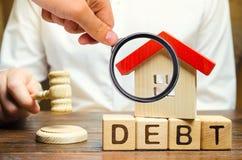 Ξύλινοι φραγμοί με το χρέος λέξης και ένα μικροσκοπικό σπίτι με το σφυρί ενός δικαστή Κατάσχεση της ιδιοκτησίας για την αποτυχία  στοκ φωτογραφία με δικαίωμα ελεύθερης χρήσης