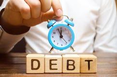 Ξύλινοι φραγμοί με το χρέος λέξης και το ρολόι στα χέρια ενός επιχειρηματία Έγκαιρη πληρωμή του χρέους Χρόνος να πληρωθούν μακριά στοκ εικόνα με δικαίωμα ελεύθερης χρήσης