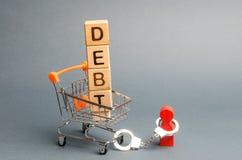 Ξύλινοι φραγμοί με το χρέος λέξης σε ένα καροτσάκι υπεραγορών και ένα ανθρώπινο ειδώλιο που δεσμεύονται από τις χειροπέδες Υποχρε στοκ εικόνα με δικαίωμα ελεύθερης χρήσης
