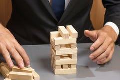 Ξύλινοι φραγμοί πύργων, το χέρι του επιχειρηματία Κίνδυνοι και προγραμματισμός στοκ φωτογραφίες
