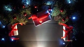 Ξύλινος μαύρος πίνακας που διακοσμείται με τα μπιχλιμπίδια Χριστουγέννων, τα δώρα και τα μπλε φω'τα Χριστουγέννων φιλμ μικρού μήκους