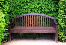 Ξύλινος πάγκος κήπων που περιβάλλεται από το πράσινο φύλλωμα Στοκ εικόνα με δικαίωμα ελεύθερης χρήσης