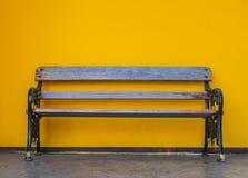 Ξύλινος πάγκος, μαύρα πόδια σιδήρου με το κίτρινο υπόβαθρο τοίχων στοκ φωτογραφία