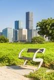 Ξύλινος πάγκος πάρκων στην ανατολή σε ένα πάρκο με ένα υπόβαθρο εικονικής παράστασης πόλης στοκ φωτογραφίες με δικαίωμα ελεύθερης χρήσης
