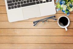 Ξύλινος πίνακας γραφείων γραφείων με το σημειωματάριο, το λουλούδι, το φλιτζάνι του καφέ και το γ Στοκ Φωτογραφίες