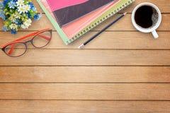 Ξύλινος πίνακας γραφείων γραφείων με το σημειωματάριο, το λουλούδι, το φλιτζάνι του καφέ και το γ Στοκ Εικόνα