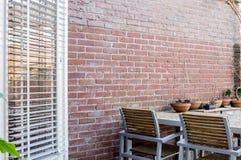 Ξύλινος πίνακας κήπων με το τουβλότοιχο στοκ φωτογραφία