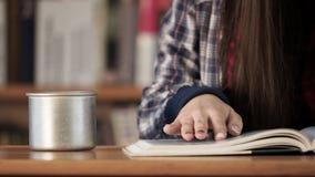 Ξύλινος πίνακας με το ανοικτό βιβλίο, το φλυτζάνι και τα θηλυκά χέρια απόθεμα βίντεο