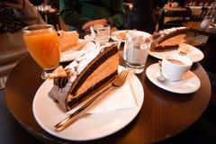 Ξύλινος πίνακας με το γιγαντιαίους κέικ, τον καφέ, τη ζάχαρη και το χυμό στοκ εικόνα με δικαίωμα ελεύθερης χρήσης