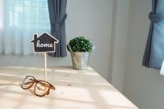 Ξύλινος πίνακας με το σημάδι σπιτιών που στέκεται, τεχνητό δέντρο στο δοχείο Στοκ φωτογραφία με δικαίωμα ελεύθερης χρήσης