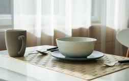 Ξύλινος πίνακας με το φλυτζάνι και πιάτο στο σύγχρονο dinning δωμάτιο Στοκ Φωτογραφία